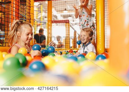Happy Kids Playing At Balls Pool Playground. Boys And Girls Playing With Multi Coloured Plastic Ball