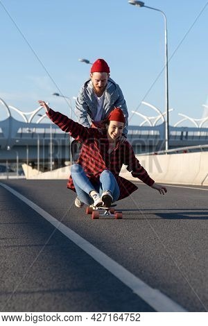 Happy Couple Of Lovers Chilling Outdoors Relaxing Ride Longboard, Laugh And Have Fun Together. Caref