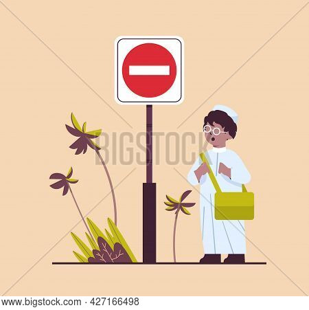 Arab Schoolboy With Backpack Standing Near Red Stop Road Sign Road Safety Concept
