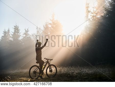 Back View Of Man Sitting On Bicycle And Raising Hands While Looking At Morning Sunlight Behind Trees