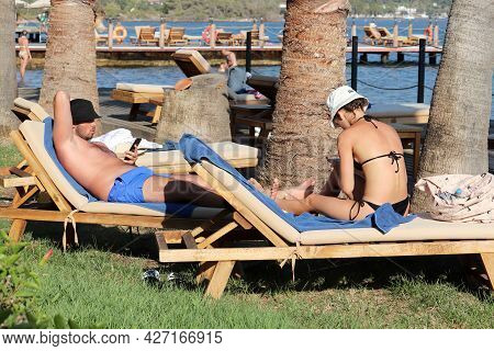 Hisaronu, Turkey - July 2021: Couple Tanning In Lounge Chairs With Smartphones In Hands Under Palm