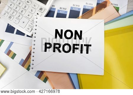 On The Financial Document Near The White Calculator There Is A Notebook On Which It Is Written A Non