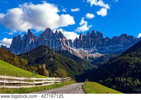 Magnificent Dolomites on a sunny autumn day. Europe, Val de Funes. Tyrol, Italy. Green grassy pastures and mountain roads are fenced with neat wooden fences