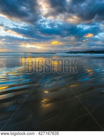Sunrise over the ocean. Gentle cloud colors are reflected in the ocean water. Light wind causes small ripples in the water. The art of artistic photography. New Zealand, Pacific Coast.