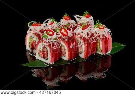 Sushi Rolls With Tuna, Unagi Sauce, Daikon On Bamboo Leaf