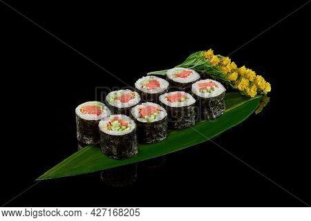 Maki Sushi Rolls With Smoked Salmon And Cucumbers On Bamboo Leaf