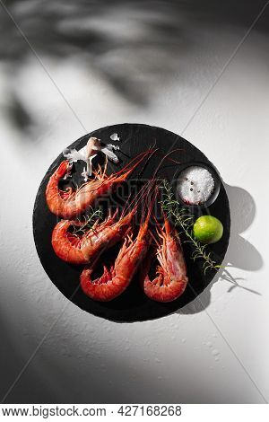 Whole Prawns On Round Slate Board With Condiments, Lime, Garlic And Rosemary