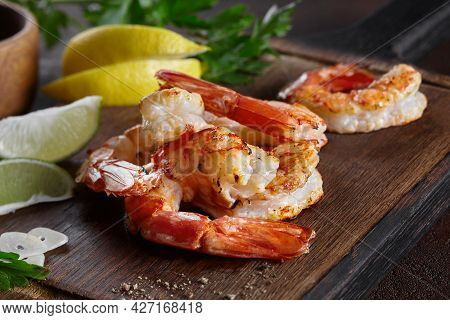 Grilled Prawn Tails With Lemon, Lime, Garlic And Greens On Wooden Board