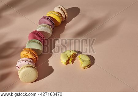 Whole Macarons Arranged In Line And One Broken Cookie