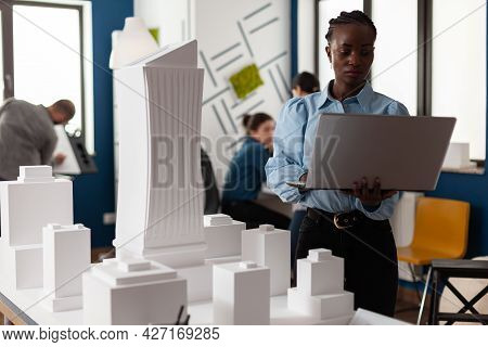 African American Architect At Business Workplace Looking At Laptop And Blueprint Plan For Building M