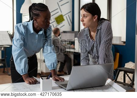 Professional Diverse Architect Women Working On Laptop Computer On Blueprint Plans For Building Mode