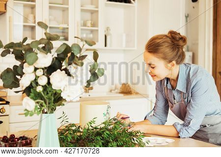 Young woman pastry chef in the kitchen decorating cake with flowers and berries.
