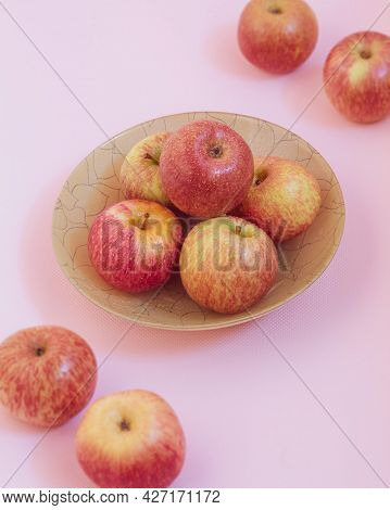 The Photo Shows An Image Of Fresh Fruit. These Are Whole And Raw Apples That Lie On A Plate And Near