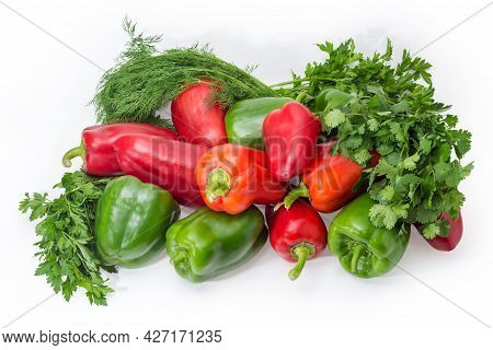 Pile Of Fresh Green And Red Bell Peppers Among The Bunches Of Parsley, Cilantro And Dill On A White