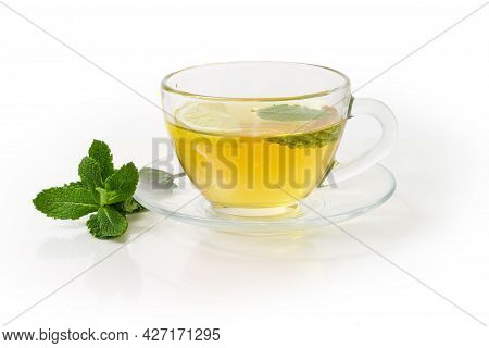 Glass Cup Of The Tea With Mint Leaf And Lemon Slice On The Glass Saucer, Twig Of Fresh Mint On A Whi