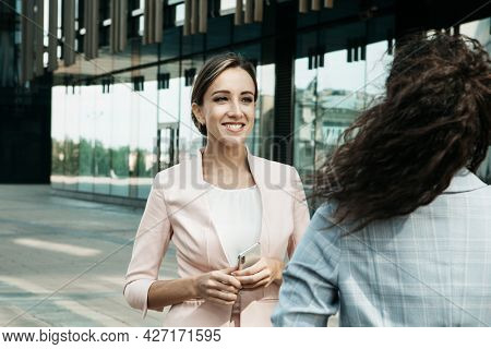 Business, people and lifestyle concept: Two business women having a casual meeting or discussion near a modern office