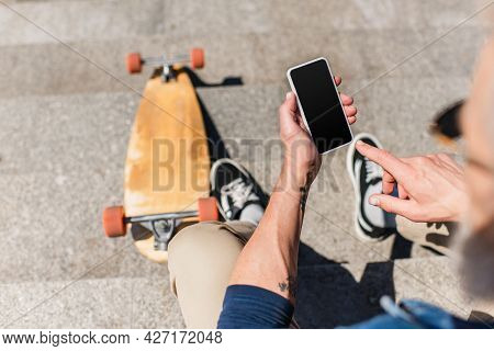 Top View Of Tattooed Mature Man Using Smartphone With Blank Screen Near Longboard On Stairs