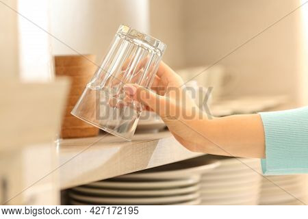 Close Up Of A Woman Hand Catching A Glass In The Kitchen