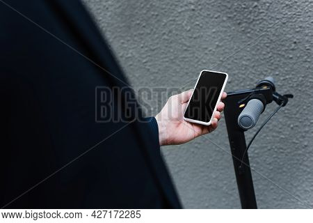 Partial View Of Mature Man Holding Smartphone With Blank Screen Near E-scooter
