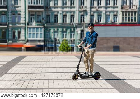 Full Length Of Middle Aged Man In Sunglasses And Helmet Riding E-scooter In Urban City