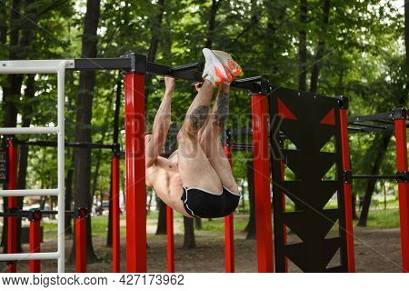 Strong Sportsman Doing Toes To Bar Abdominal Exercise Outdoors