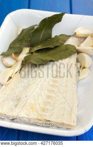 Salted Cod Fish With Bay Leaf On Dish On Wooden Background