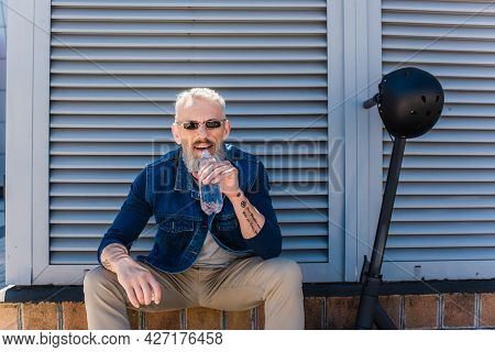 Bearded Mature Man In Sunglasses Smiling And Drinking Water Near E-scooter With Helmet