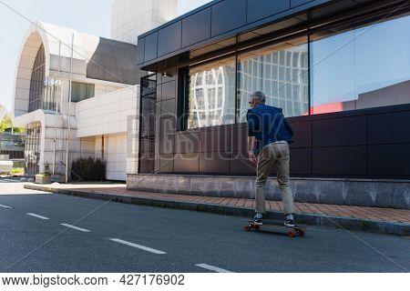Back View Of Mature Man Riding Longboard On Urban Street