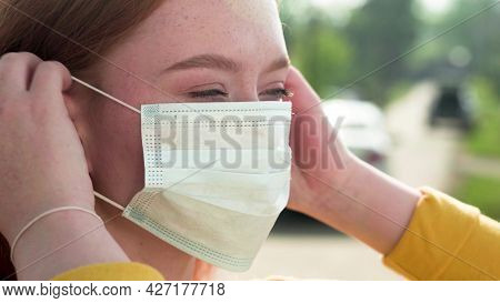 Redhead Girl With Freckles Puts On A Medical Mask While Standing On The Street. A Young Woman Puts A