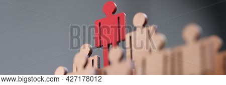 Red Wooden Figurine Standing Above Others Closeup