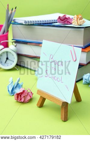 A Small Easel With A Sticker With The Inscription Back To School On The Background Of The Educationa