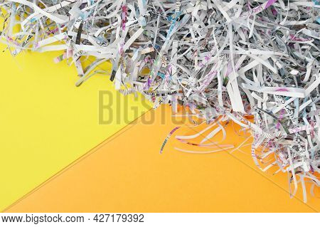 Shredded Paper On Light Yellow And Orange Background. Selective Focus Image.