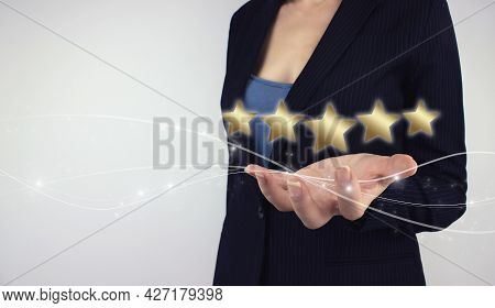 Five Stars 5 Rating Concept. Hand Hold Digital Hologram Five Gold Stars On Grey Background. Review,