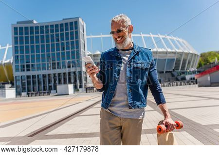 Happy Middle Aged Man In Sunglasses Holding Longboard While Using Cellphone On Urban Street
