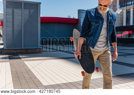 Bearded Middle Aged Man In Sunglasses Holding Longboard On Urban Street