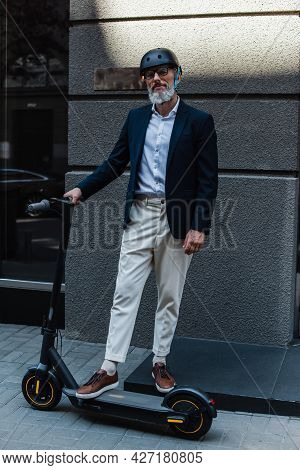 Full Length Of Middle Aged Businessman In Blazer And Helmet Near E-scooter