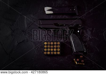 Flat Lay Of Cartridges And Gun On Concrete Background. Top View With Copy Space. Pistol And Bullets