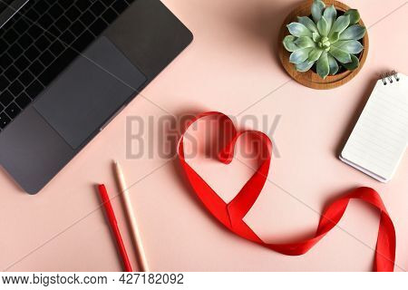 Heart From Red Ribbon, Laptop, Plant And Notebook On Pink Desk Background. Concept Valentines Day, O