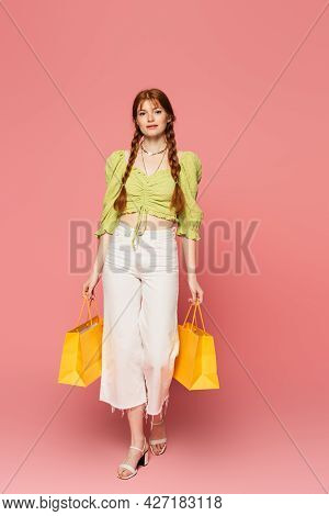 Pretty Woman With Freckles Holding Shopping Bags On Pink Background