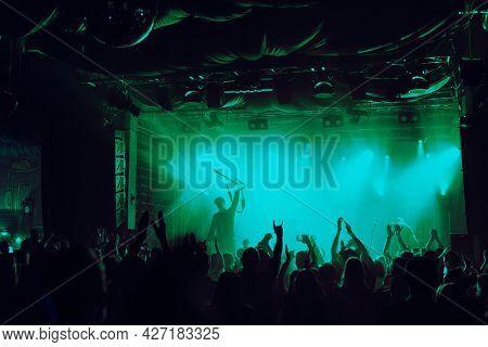Cheering crowd having fun at music festival in a nightclub