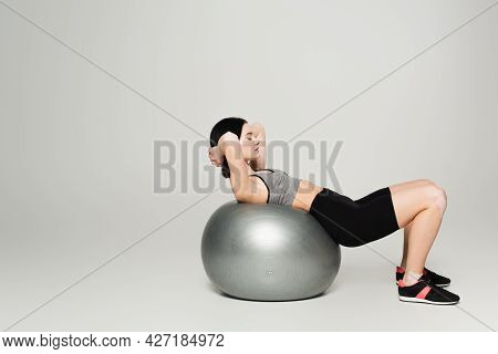 Side View Of Sportswoman With Vitiligo Working Out On Fitness Ball On Grey Background