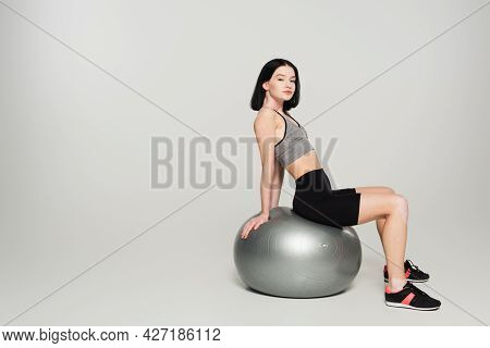 Sportswoman With Vitiligo Sitting On Fitness Ball On Grey Background