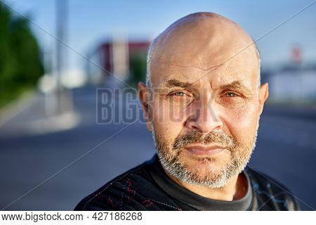 Bald Elderly Man With Gray Stubble In Front Of City Street.