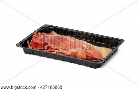 Sliced Prosciutto Meat In Thin Slices In Black Plastic Packaging On A White Plate