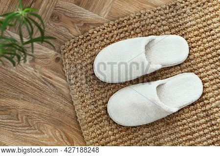White indoor slippers on jute rug