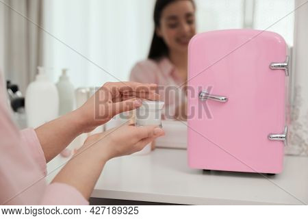 Woman Getting Ready At Dressing Table With Cosmetic Refrigerator Indoors, Closeup