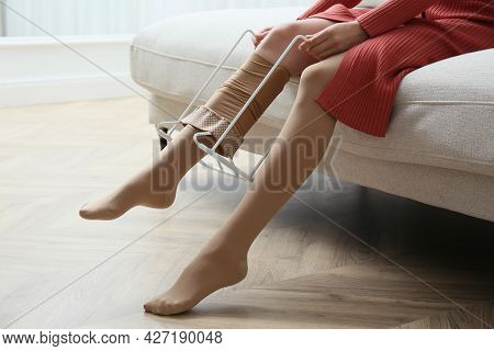 Woman Wearing Compression Tights With Donner On Sofa Indoors, Closeup