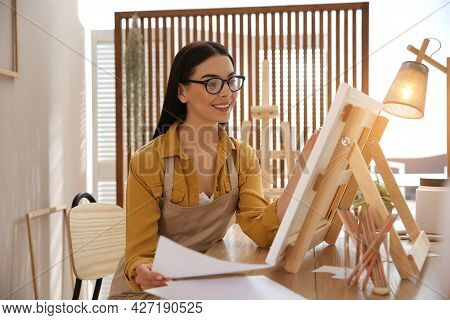 Young Woman Drawing On Easel At Table Indoors