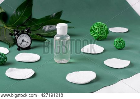 Make-up Remover In Small Bottle, Alarm Clock And Cotton Discs On Green. Cleansing Skin At Night And