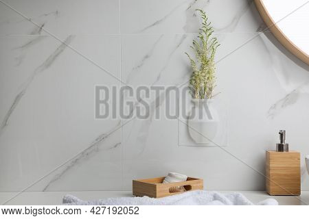 Silicone Vase With Flowers On White Marble Wall In Stylish Bathroom. Space For Text